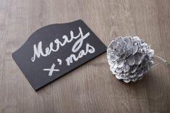 Muestra del texto de la Feliz Navidad con el ornamento del cono del pino Imagen de archivo libre de regalías