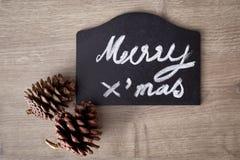 Muestra del texto de la Feliz Navidad con el ornamento del cono del pino Fotos de archivo libres de regalías