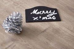Muestra del texto de la Feliz Navidad con el ornamento del cono del pino Fotografía de archivo libre de regalías