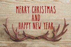 Muestra del texto de la Feliz Navidad en los ornamentos del reno con la tarjeta de felicitación y en fondo de madera rústico Conc imagenes de archivo