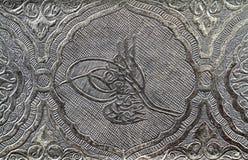 Muestra del tugra del otomano tallada y modelada en la superficie de plata Foto de archivo