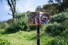 Muestra destrozada de la advertencia/de la precaución de la serpiente de cascabel en el parque imágenes de archivo libres de regalías