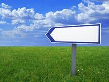 Muestra en blanco de la flecha, cielo azul e hierba verde Imagen de archivo libre de regalías
