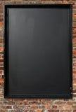 Muestra en blanco del menú de la pizarra en una pared de ladrillo roja. Fotografía de archivo libre de regalías