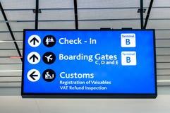 Muestra en el aeropuerto internacional - direcciones de la información para el enregistramiento y las puertas Imagen de archivo libre de regalías