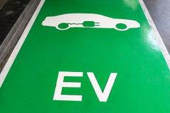 Muestra enchufable blanca del vehículo con el alfabeto EV en estacionamiento verde imagen de archivo libre de regalías
