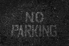 Muestra erosionada del estacionamiento prohibido pintada en blanco en el asfalto oscuro Imágenes de archivo libres de regalías