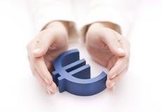 Muestra euro protegida por las manos Imagenes de archivo