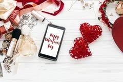 Muestra feliz del texto del día de tarjetas del día de San Valentín en la pantalla y el lujo elegantes del teléfono Imagen de archivo
