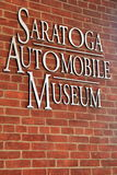 Muestra grande del metal en la pared de ladrillo de la entrada, museo auto de Saratoga, Nueva York, 2015 Fotografía de archivo libre de regalías