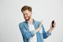 Muestra hermosa joven descontentada de la parada de la demostración del hombre de llamar por teléfono en otra mano que mira la cá Foto de archivo libre de regalías