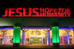 Muestra iluminada Jesús sobre la entrada de la iglesia Fotos de archivo