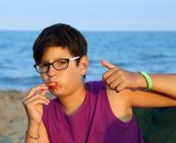 Muestra joven de la AUTORIZACIÓN del muchacho con el pulgar para arriba que come la pizza Foto de archivo libre de regalías