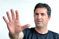 Muestra madura trastornada de la parada de la demostración del hombre con su palma. fotografía de archivo