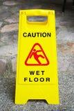 Muestra mojada del piso de la precaución en la calzada Fotografía de archivo libre de regalías