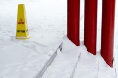 Muestra mojada plástica amarilla del piso en piso nevado. Imagenes de archivo