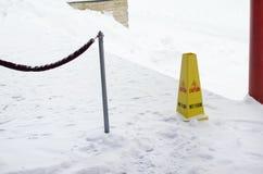 Muestra mojada plástica amarilla del piso en piso nevado. Foto de archivo