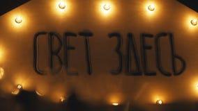 Muestra retra, adornada con las luces eléctricas Inscripción la luz aquí Imagen de archivo libre de regalías