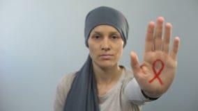 Muestra roja de la cinta en el gesto de la parada de la demostración de la palma de la mujer, campaña de concienciación de las AY almacen de metraje de vídeo