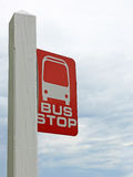 Muestra roja y blanca de la parada de autobús otra vez un cielo tempestuoso gris Foto de archivo