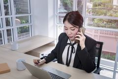 Muestra sonriente de la empresaria joven un documento y el hablar con el teléfono imagen de archivo