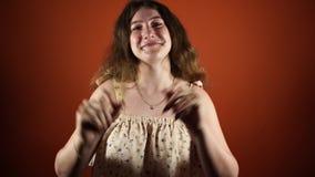 Muestra y mirada morenas sonrientes de la autorización de la demostración de la mujer de la cámara sobre fondo anaranjado almacen de video