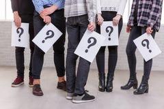 Muestran un grupo de personas incompleto con sus manos abajo en cuál las hojas con el signo de interrogación Imagenes de archivo