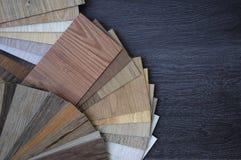 Muestras de baldosa de la lamina y del vinilo en el fondo de madera wo imágenes de archivo libres de regalías