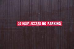 24 muestras del estacionamiento prohibido del acceso de la hora rojas y blancas en puerta de acceso de madera fotos de archivo libres de regalías