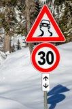 Muestras del límite del cuidado y de velocidad en un camino cubierto en nieve Fotos de archivo