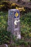 Muestras direccionales en la manera de San Jaime Cáscara de concha de peregrino y flecha amarilla con el fondo azul en una pared  Fotografía de archivo libre de regalías