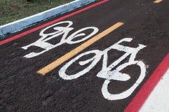 Muestras en la tierra para los ciclistas pista del carril de la bici Derecho venir e ir a completar un ciclo solamente Foto de archivo libre de regalías