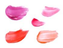 Muestras manchadas de los lipgloss aisladas en blanco Imagenes de archivo