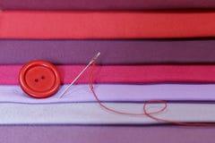 Muestras multicoloras de la tela Botón con una aguja y un hilo encendido foto de archivo