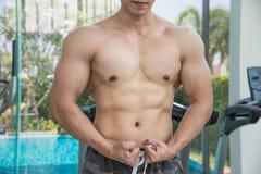 Muestre al cuerpo de los músculos del hombre hermoso en el gimnasio o el centro de aptitud Foto de archivo