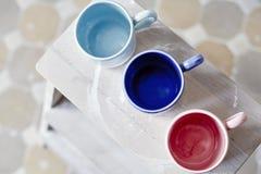 Muestrea las tazas coloreadas de cerámica hechas a mano en la tabla de madera, trabajando proceso en estudio Fotografía de archivo