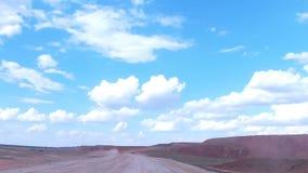 Mueva la cámara adelante a lo largo del camino a la mina a cielo abierto detrás del coche en el horizonte almacen de video