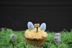 Muffin överträffade med en miniatyrpersonstatyett som rymmer ett tecken, indikera som jag älskar påsk med ägggarneringar för någr royaltyfria foton