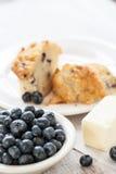 Muffin βακκινίων που κόβεται στο μισό με το βούτυρο και το κύπελλο των βακκινίων Στοκ φωτογραφία με δικαίωμα ελεύθερης χρήσης