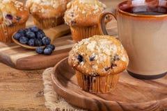 Muffin και φλιτζάνι του καφέ βακκινίων σε ένα ξύλινο πιάτο στοκ εικόνες με δικαίωμα ελεύθερης χρήσης