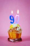 Muffin με το κάψιμο των κεριών γενεθλίων ως αριθμό ενενήντα Στοκ Εικόνες