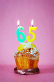 Muffin με το κάψιμο των κεριών γενεθλίων ως αριθμό εξήντα πέντε Στοκ Εικόνες