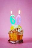 Muffin με το κάψιμο των κεριών γενεθλίων ως αριθμό εξήντα Στοκ Εικόνες