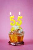 Muffin με το κάψιμο των κεριών γενεθλίων ως αριθμό πενήντα πέντε Στοκ Εικόνες