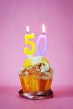 Muffin με το κάψιμο των κεριών γενεθλίων ως αριθμό πενήντα Στοκ Εικόνες