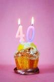 Muffin με το κάψιμο των κεριών γενεθλίων ως αριθμό σαράντα Στοκ Εικόνες