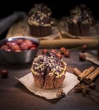 Muffin που ψεκάζεται με τα καρύδια σε ένα καφετί κομμάτι του χαρτί του Κραφτ Στοκ Εικόνα