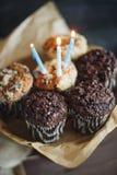 Muffin σοκολάτας γενεθλίων με τρία κεριά στο μαύρο υπόβαθρο Στοκ Φωτογραφίες