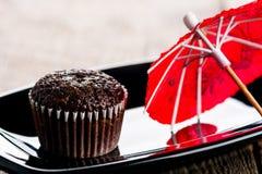Muffin σοκολάτας και κόκκινη ομπρέλα Στοκ Φωτογραφίες