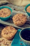 Muffin σοκολάτας τη μαλακή κρέμα και το φρέσκο βακκίνιο που κονιοποιούνται με με τη ζάχαρη, φλιτζάνι του καφέ, αγροτικό υπόβαθρο Στοκ εικόνες με δικαίωμα ελεύθερης χρήσης